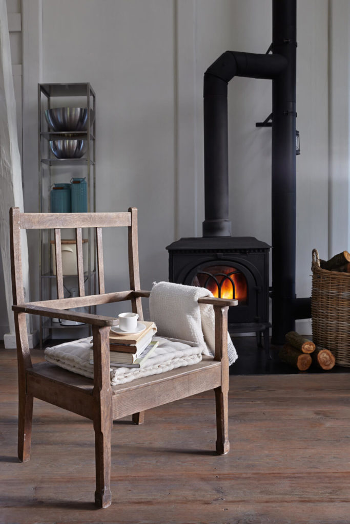 Moving into the living room space, we see an old restored wood chair in front of a traditional black pot-belly stove.