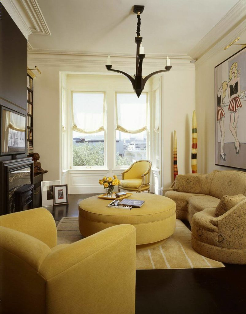 A small sitting room off of one of the bedrooms is in a bit bolder yellow and has an enormous yellow ottoman that doubles as a coffee table in front of the dark marble fireplace.