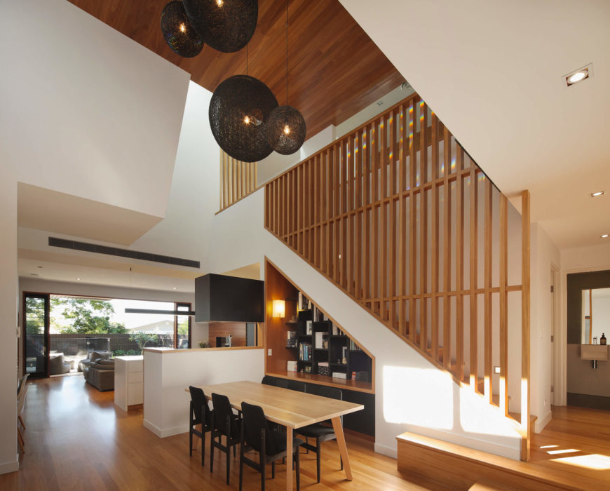 In this open space, we see the dining room defined by its relationship to the staircase. Rich hardwood tones spread everywhere, contrasting perfectly with the white and dark grey hues.