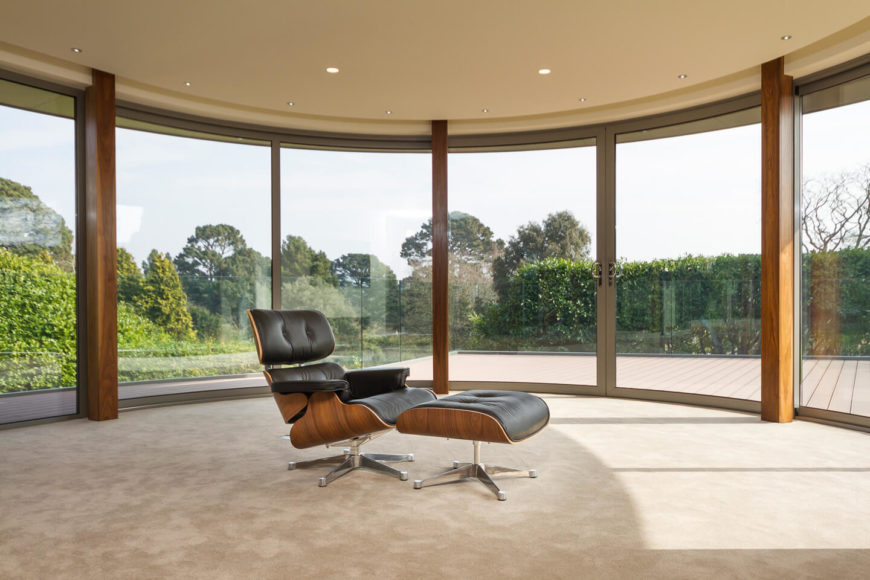 This circular space enjoys the wraparound, curved glass treatment seen in the primary bedroom, with a pair of sliding doors at center opening to the vast balcony. Natural wood exposed beams add an element of rich nature to the modern space.