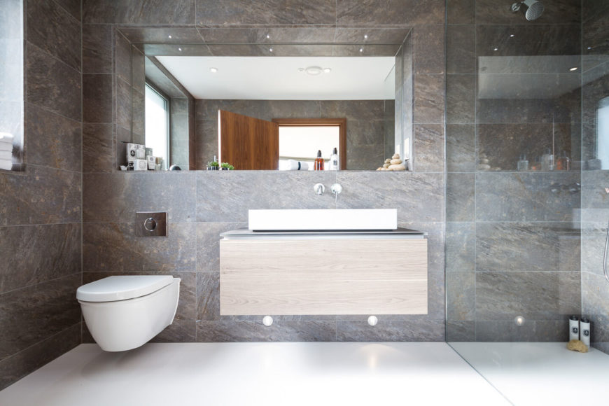The bathroom features large format granite wall tiling over a pristine white floor, with floating natural wood vanity at center. A glass enclosed walk-in shower fills the space at right.