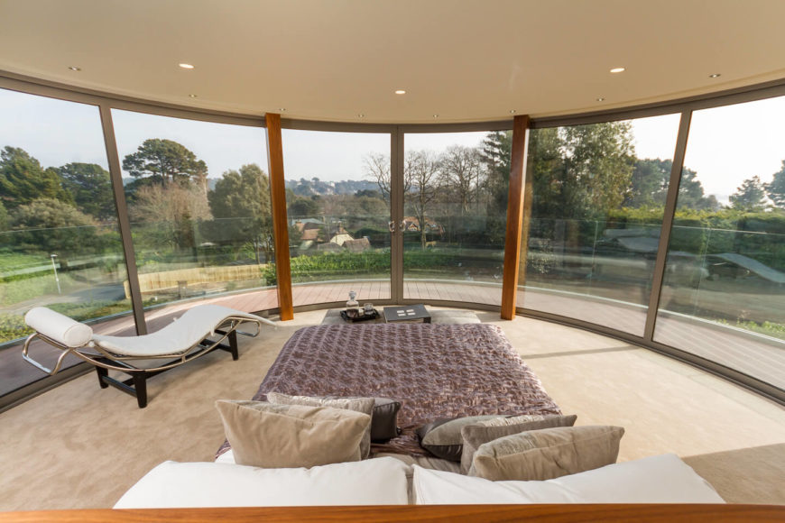 The primary bedroom, on an upper floor, enjoys panoramic views courtesy of the wraparound full height glazing and unobstructed surroundings. The simple, cleanly designed room features a small table at the foot of the bed, and ultra-modern chaise lounge at left.