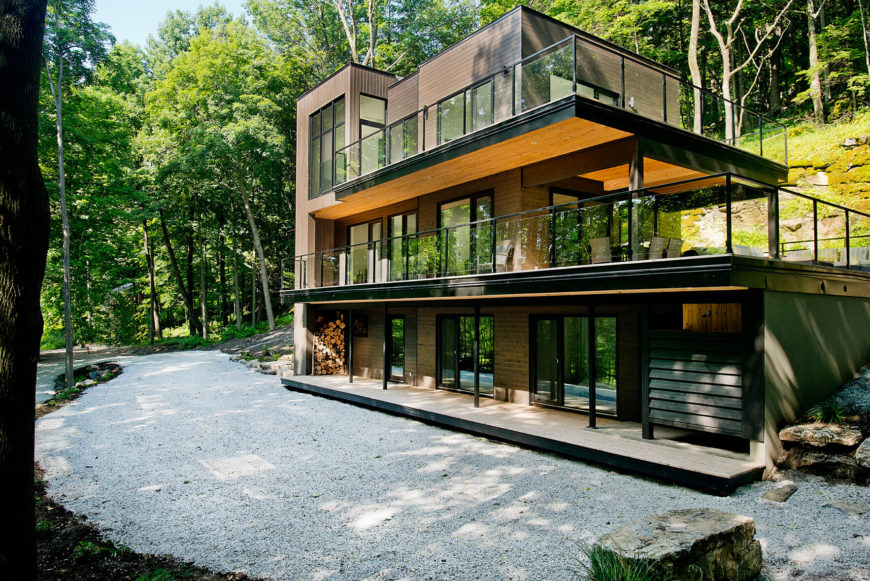 With the full home in view, we see the mixture of wood tones and black metal framing that create the angular, tiered structure. The front is fully exposed while the back recedes into the hillside.
