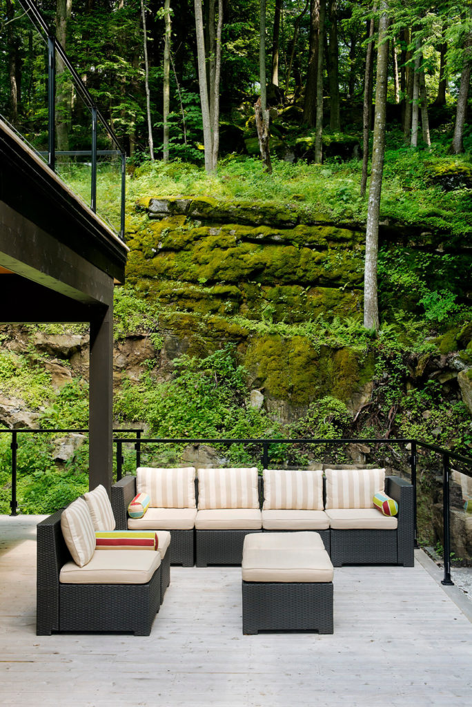 On the lower terrace, this grey rattan sectional stands against the hillside, offering expansive views from a comfortable position.