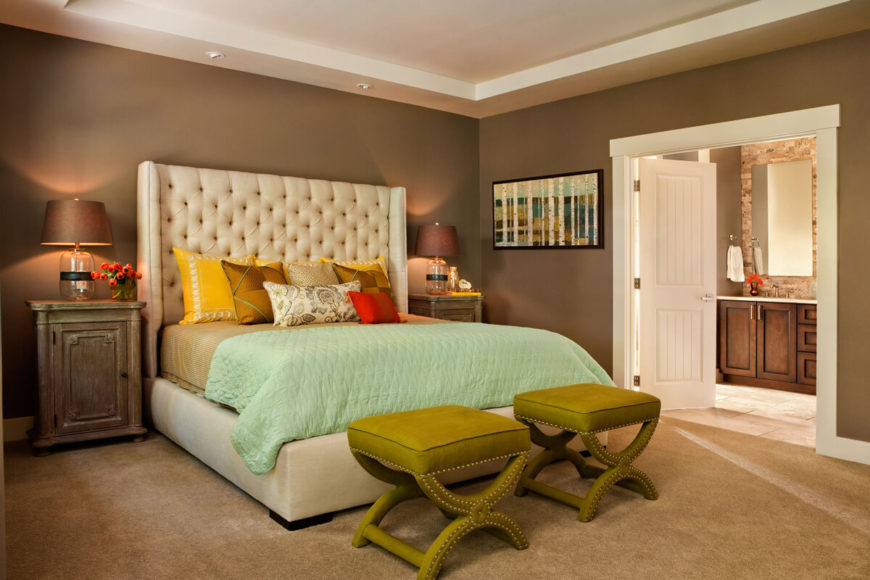 With a pair of white double doors leading to the en suite bathroom, the primary bedroom expands its footprint. A pair of green hued ottomans stand at the foot of the bed.