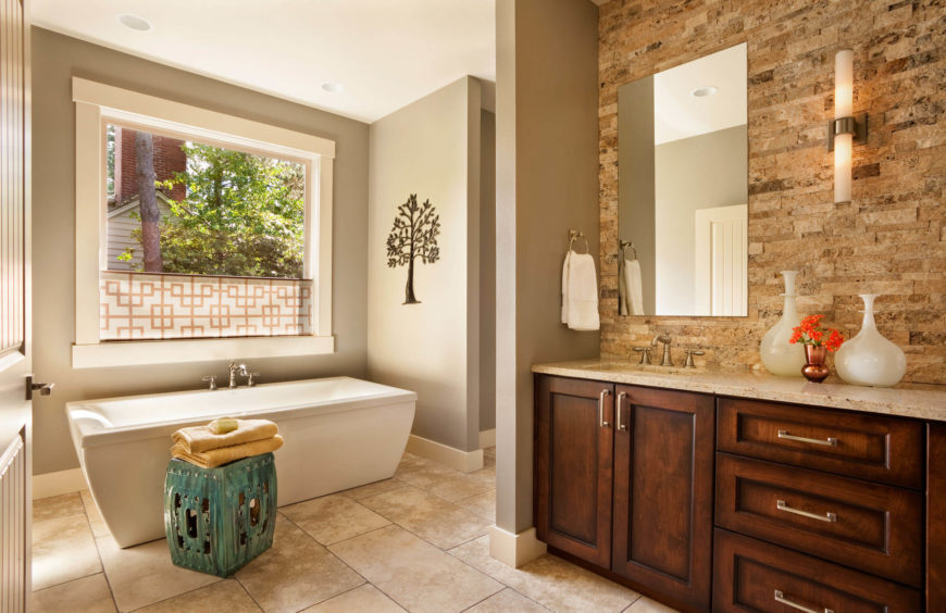 The expansive primary bath spreads over large format tile flooring, with contemporary soaking tub beneath a large window at left, and other facilities tucked around a private corner at center.