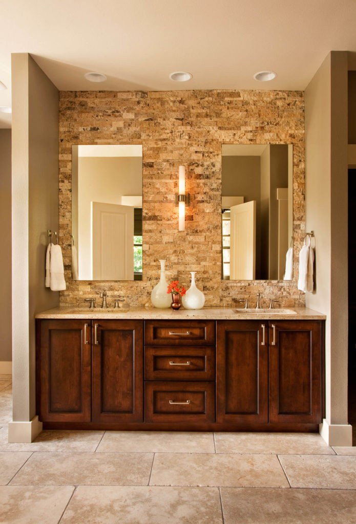Rich wood double vanity in the primary bath is topped with a granite countertop, while frameless mirrors hang on the stone brick wall above.