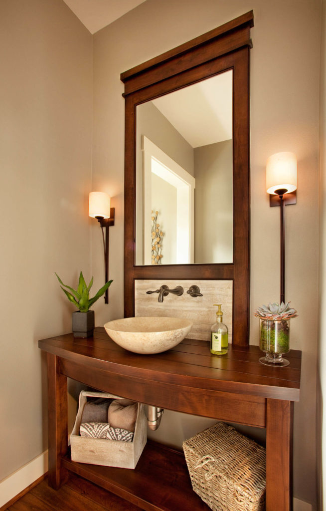 One of the bathrooms features this bespoke dark wood vanity, with marble vessel sink and backsplash beneath a tall mirror built into the frame. A pair of thin, lampshade sconces flank the piece.