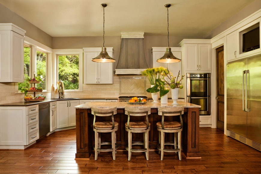 The kitchen centers on a massive natural wood island with granite countertop, offering plenty of space for cook prep and dining, courtesy of a trio of rattan seat bar stools. White cabinetry and black countertops throughout add contrast and detail.