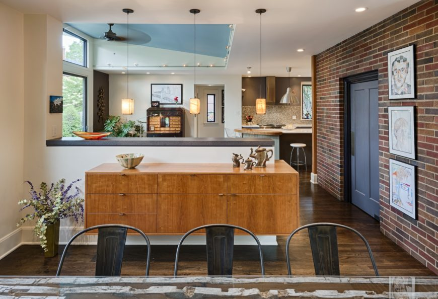 The original brick can be seen at right, contrasting with the sleekly modern surroundings. Ample daylight spills in via the large windows and raised ceiling above the family room.