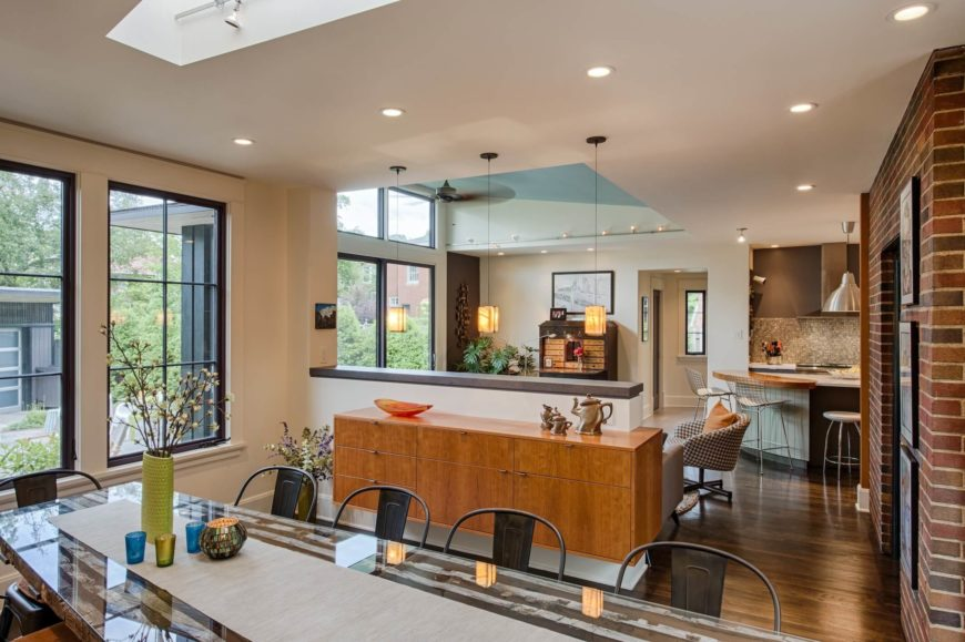 Here we see the open-plan expanse moving from the dining room to the kitchen. Sleek wood cabinetry adorns the low dividing wall, while the expanse of hardwood flooring connects each of the gradients of style as the home moves from original to new space.