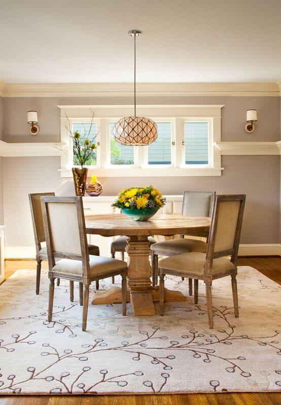 The contemporary dining room is in light gray with molding around the room, meeting at the center of the windows. Built-ins, like those in the living room, are beneath the windows and act as a buffet. The lighter wood table keeps the room from feeling small and dark.