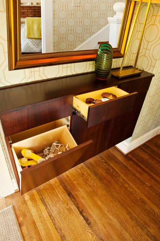 A close up on the added storage showing the way the bottom drawers lean out to store a multitude of shoes. The top drawers pull out to store sunglasses, keys, or whatever you may need. The sleek design ensures that the space doesn't feel cluttered.