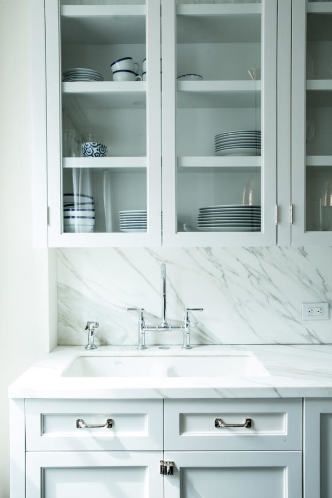 White cabinetry gives way to a sleek marble countertop and matching backsplash, with glass door cabinetry above offering a transparent look that expands the visual detail of the kitchen.