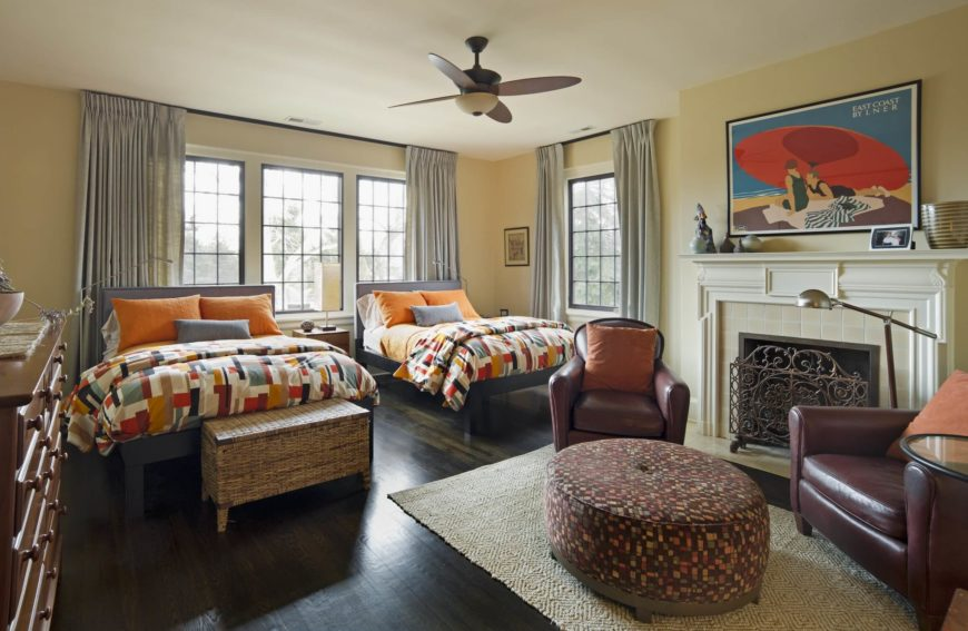 The guest bedroom features a pair of large beds, in addition to a furniture set near the fireplace, including a pair of leather club chairs and multicolored ottoman.