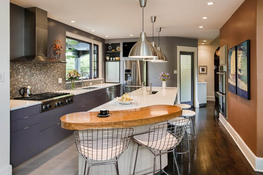 The expansive kitchen centers on the lengthy white island with raised hardwood bar at the end. Sleek cabinetry, stainless steel appliances, and an intricate tile backsplash add visually arresting detail.