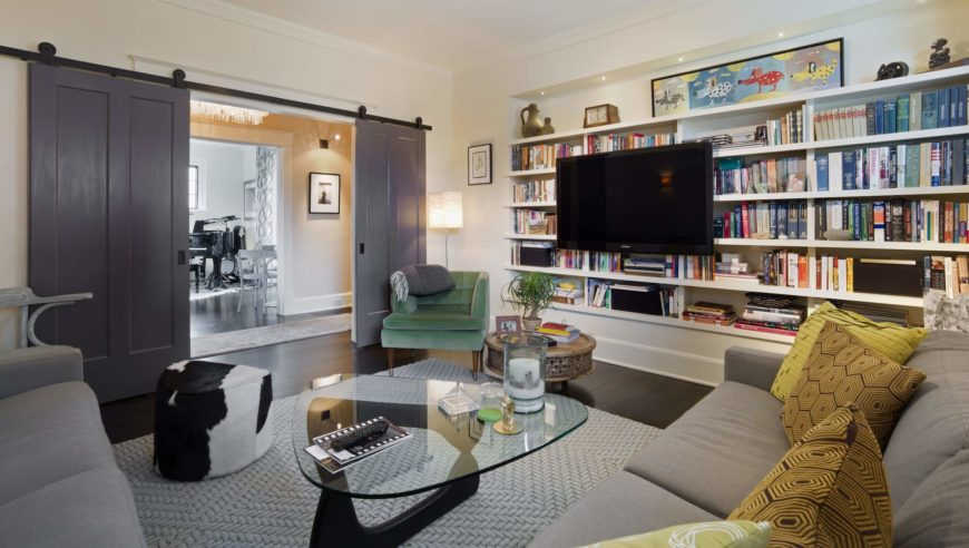The media room features an extensive library mounted on built-in shelving, with a large L-shaped sectional and ultra-modern glass table filling out the space. Large double sliding doors add privacy.