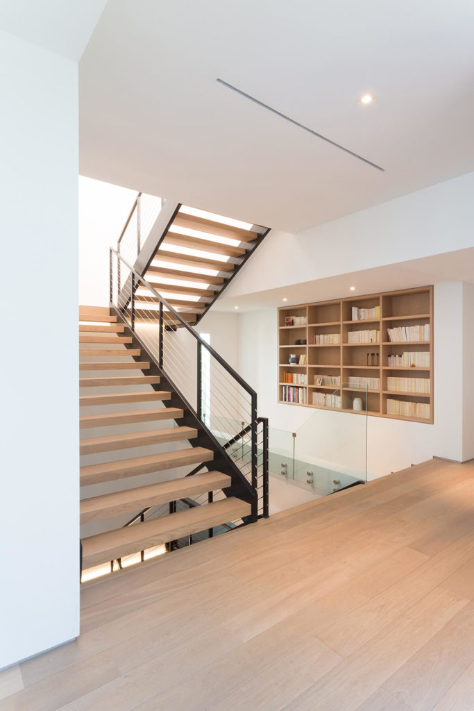 Staircases within the home are open-design mixtures of metal and timber, flanked by glass panels for ultimate visibility. Subtle natural wood shelving is built into the wall here.