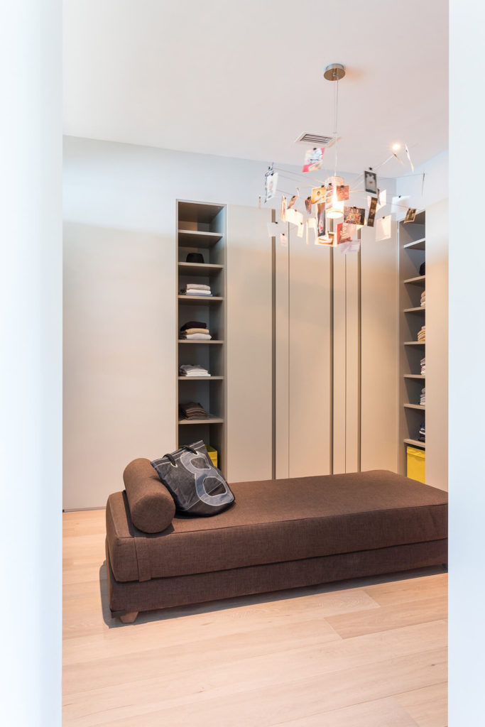 This cozy space features abundant built-in storage surrounding a contemporary brown chaise lounge. A unique photograph-dotted chandelier hangs above.