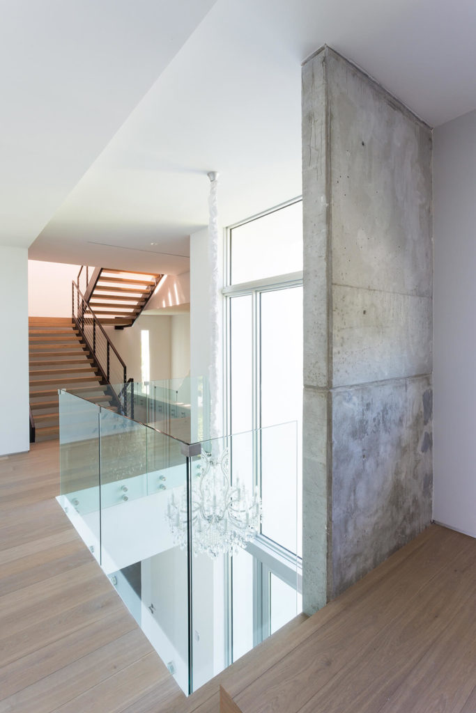 Low slung glass walls wrap the upper floor, allowing for views down into the foyer here.