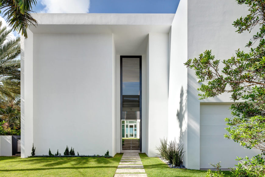 The front of the home is monolithic white, saving most of the open expanse of glass for the water-facing side.