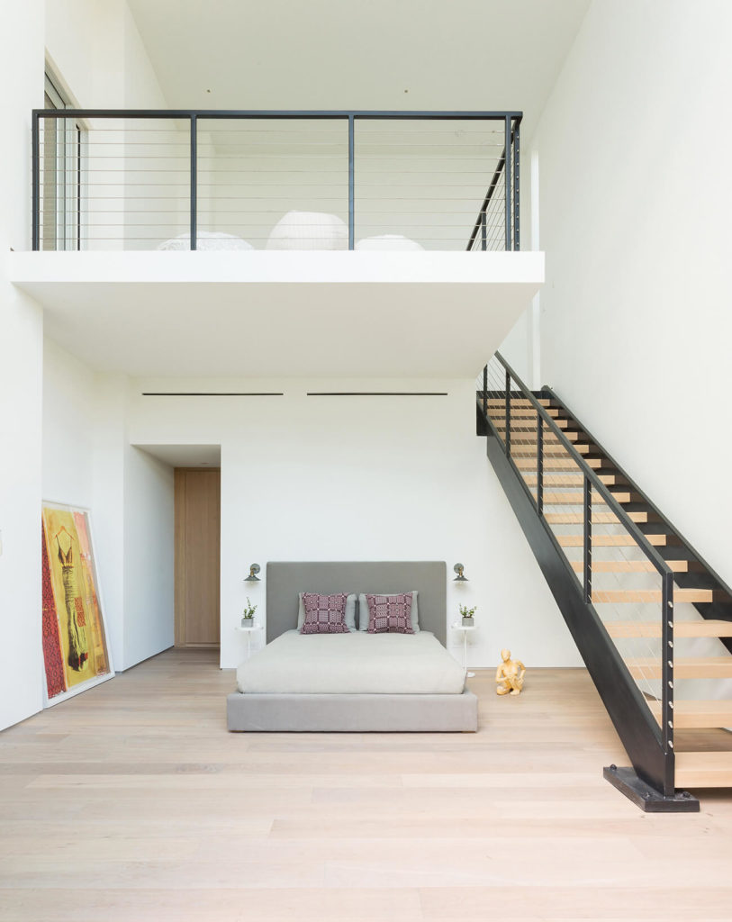 This bedroom, featuring a private loft area, enjoys a surfeit of open space over its natural hardwood flooring.