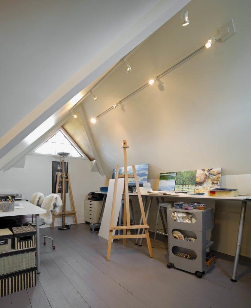 The upper floor features a unique study, with drafting tables and art supplies standing below the slim vaulted ceiling.