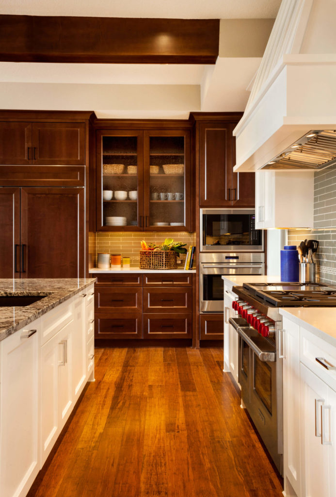 The warm tone of the wood floors is an interesting mix with the dark and white cabinetry.
