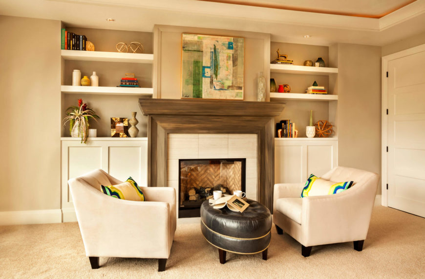 A small sitting room with an enclosed fireplace and open shelving built into the walls on either side of the fireplace.
