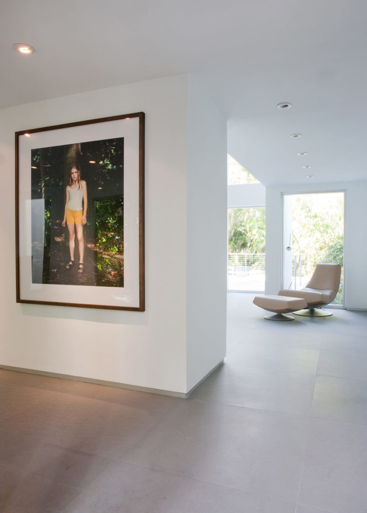In this intermediate space, we see one of many art prints on the wall, a large portrait offering a burst of color amidst the cool neutral tones of the home.