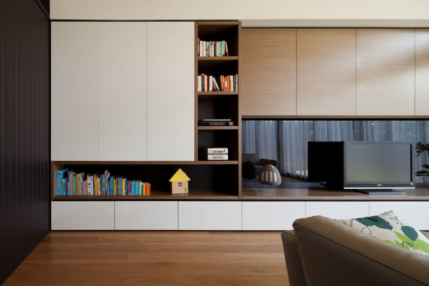 Here, we can see the far wall and its onyx tones, striking a perfect contrast between the white compartments on the far wall and the light grains in the space about the entertainment center. The owners added an endearing accessory near a selection of children's books, which lends a more nature feel to the shelf area.