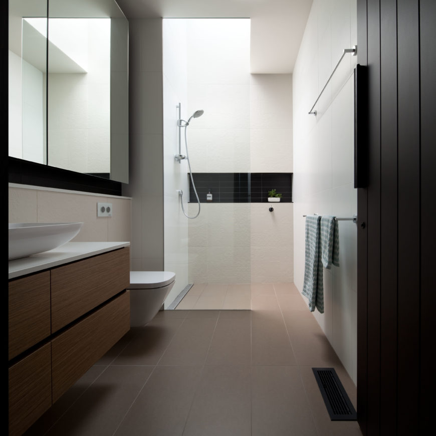 Upon entering the bathroom, the contemporary aesthetic is evident and the showering area is awash by the addition of a skylight. The owners add a small splash of color with the addition of a small plant in the shower area.
