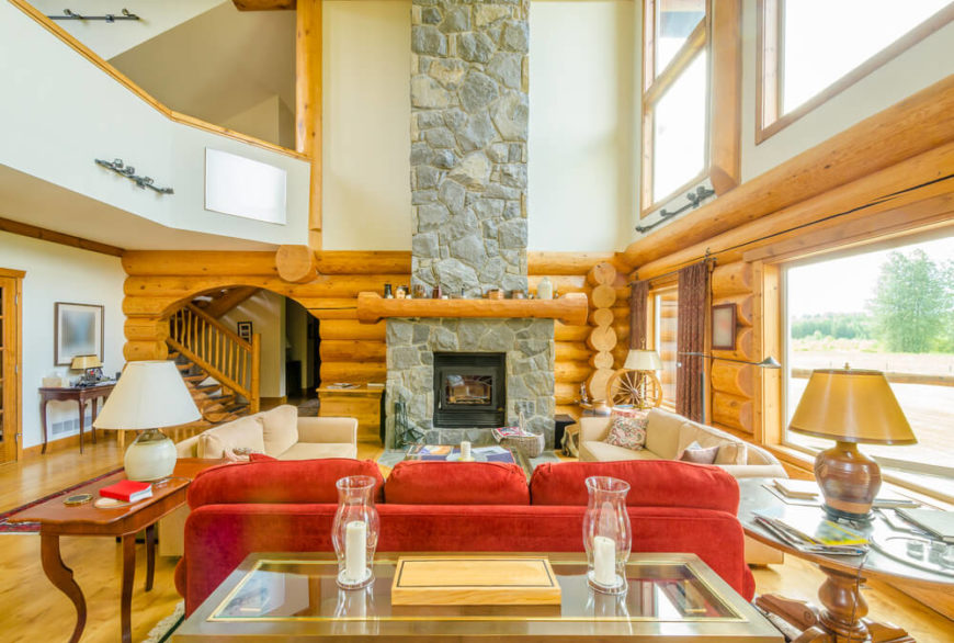 A modernized log cabin with an enormous stone fireplace. The wooden mantle is wider than the fireplace itself. An archways leads into the home's foyer and to an all-wood staircase.