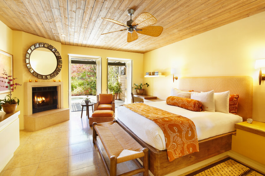 A breezy bedroom for the tropics in yellow and bright orange with natural fiber seating and rattan fan blades. The ceiling is natural wood, which is a sharp contrast to the tile flooring.