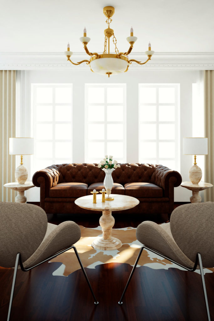 These rich dark wood floors vary very little in tone and complement the button-tufted leather sofa against the stately windows. A light cream marble table sits on a white and beige cowhide rug.