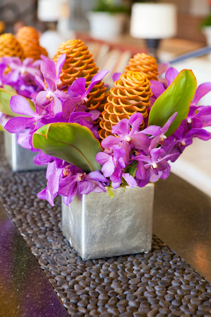 A simple vase painted in metallic silver is the perfect contrast to the beautiful vivid purple orchids and orange pinecone ginger flowers.