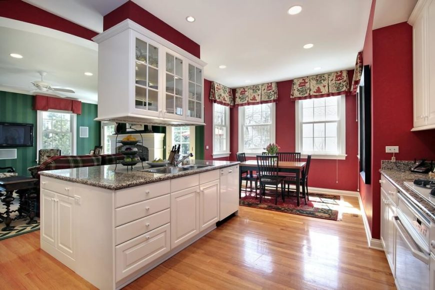 Everything about this kitchen is daring and bold. The colonial designed windows allow enough light to accentuate the adventurous red walls and polished marble counter tops.