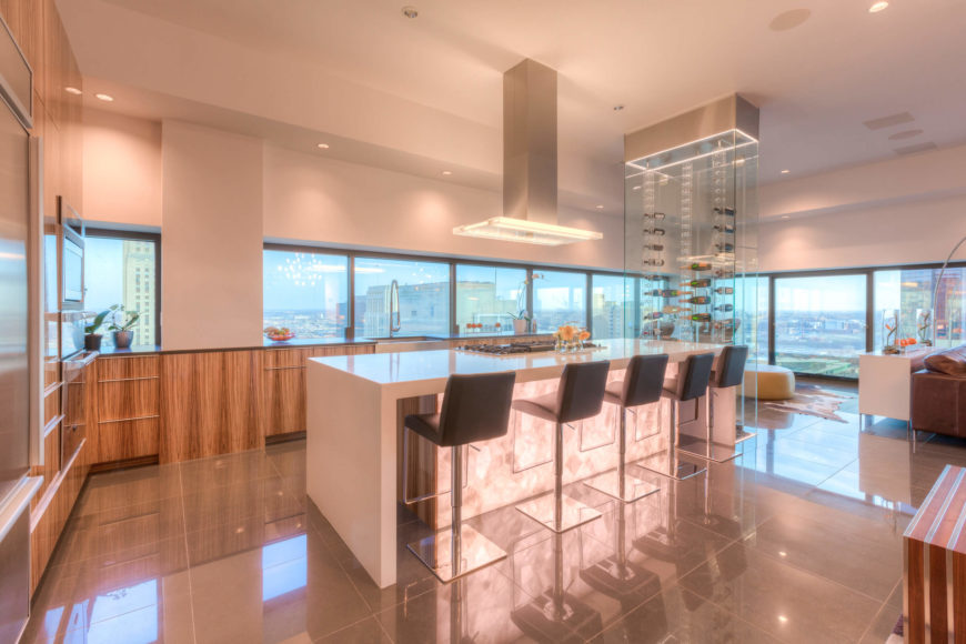 """The kitchen centers on a large, sleek white island with ample barstool seating and a built-in range. Natural wood cabinetry surrounds the island in contrast, with countertops spreading below the immense, nearly full-height windows surrounding. The """"floating"""" glass wine rack can be seen towering at right."""
