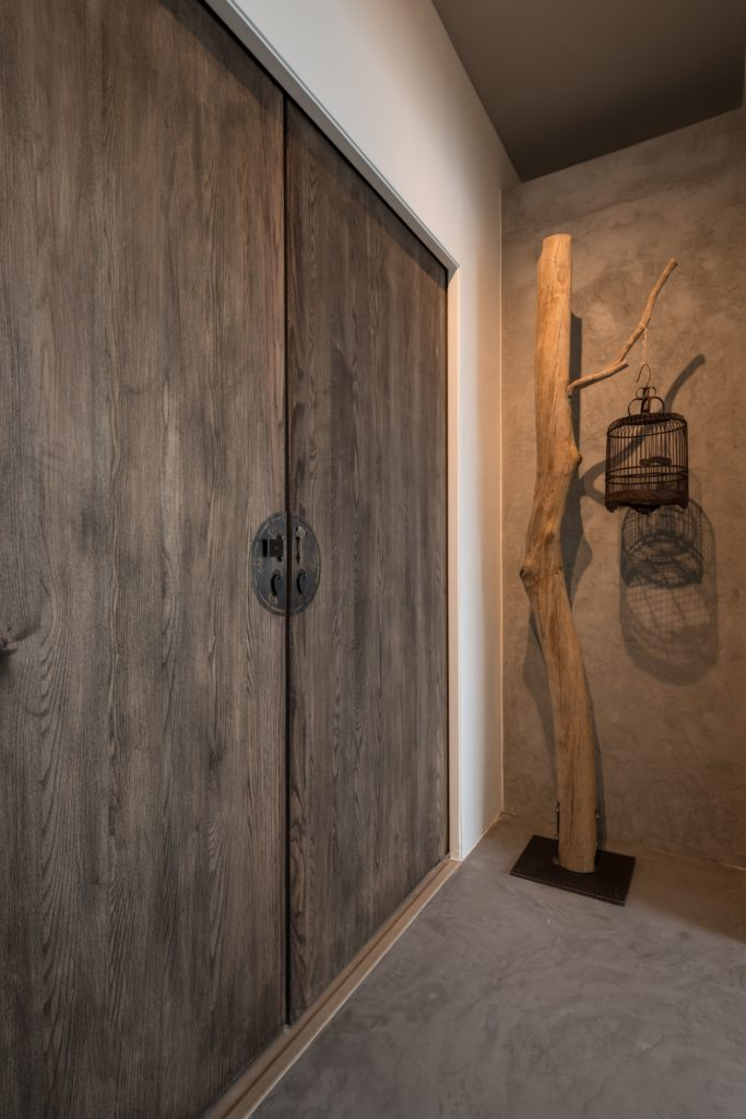 This closet space is a prime example of the wood themes found throughout the house. Opting for a more natural look, the decorative cage stand retains its limb shape.