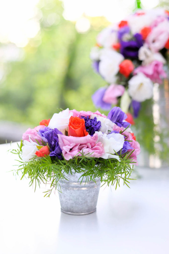A more rustic-chic centerpiece in a re-purposed tin bucket. The flowers are roses and other large blooms in white, pink, purple, and salmon.