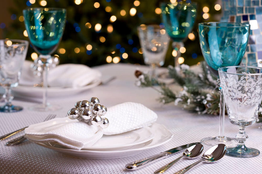 A table setting for a holiday party. Etched water goblets are paired with light blue wine glasses and silverware with a delicate gold filigree on the handles. The napkin rings have silver bubbles attached.