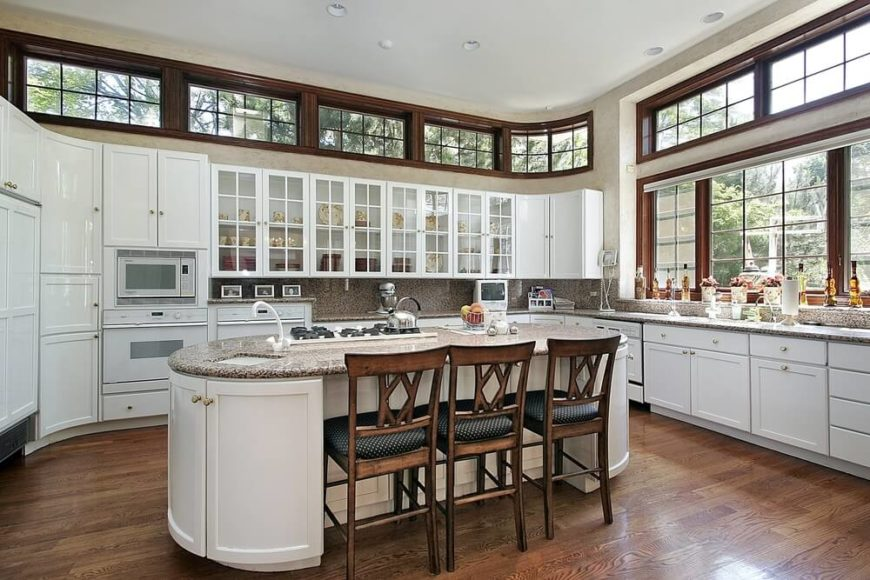This design has a lot of great contrast between the wooden window panes, the dark hardwood flooring, and the curved white cabinets. The colonial styled windows are surrounded in a dark wood and stand out in this brilliant kitchen.