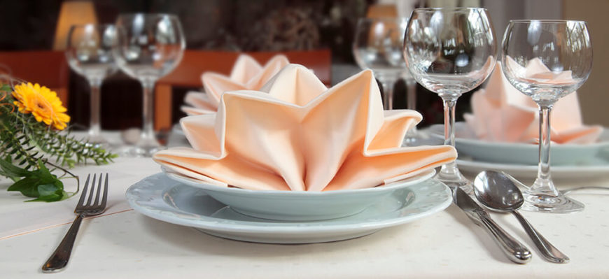 A contemporary table setting with scallop-rim dishes and peach napkins folded artfully and placed into the soup bowl.