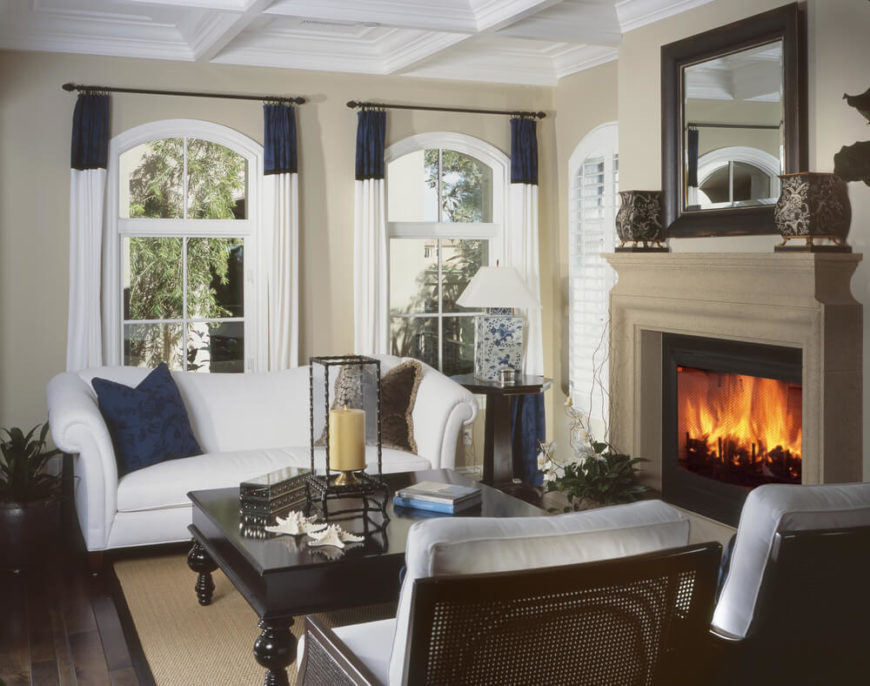 The dark wood floors of this modestly sized but comfortable living room are covered by a natural fiber area rug that lends a nautical feel to the blue and white color pallet.