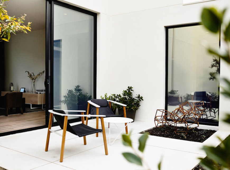 The full patio is in white tile with mirrored one-way glass to the right. A modern sculpture adds visual interest to this simple outdoor retreat.