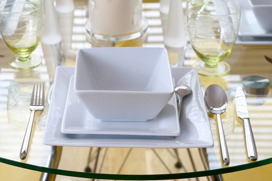 A place setting on a glass-top table with white square dishes. The base of the water goblets are a light yellow-green.