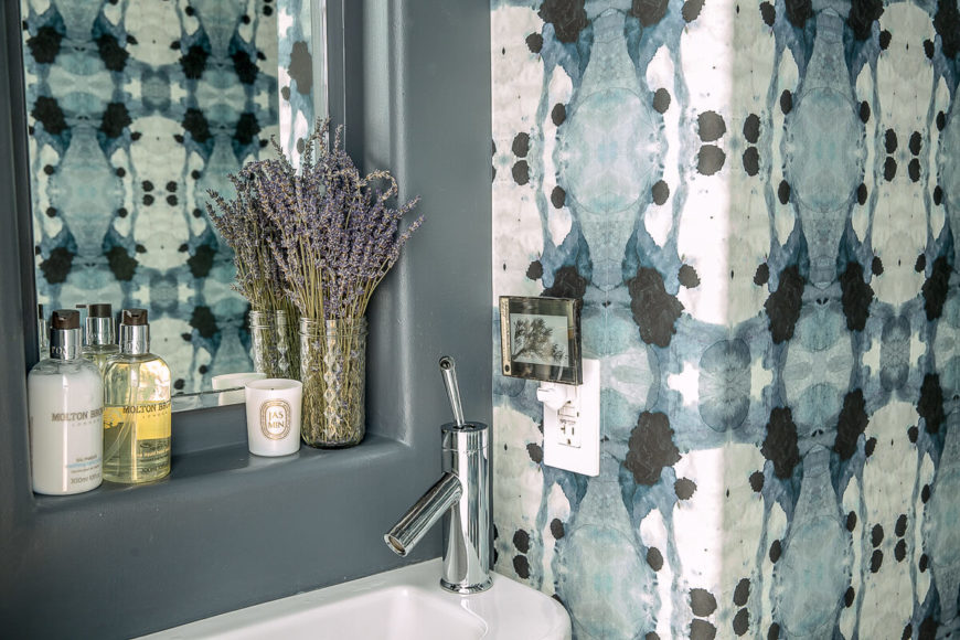 A small half-bath on the main floor is in a gorgeous blue and white. A lone pedestal sink sits below an inset mirror.