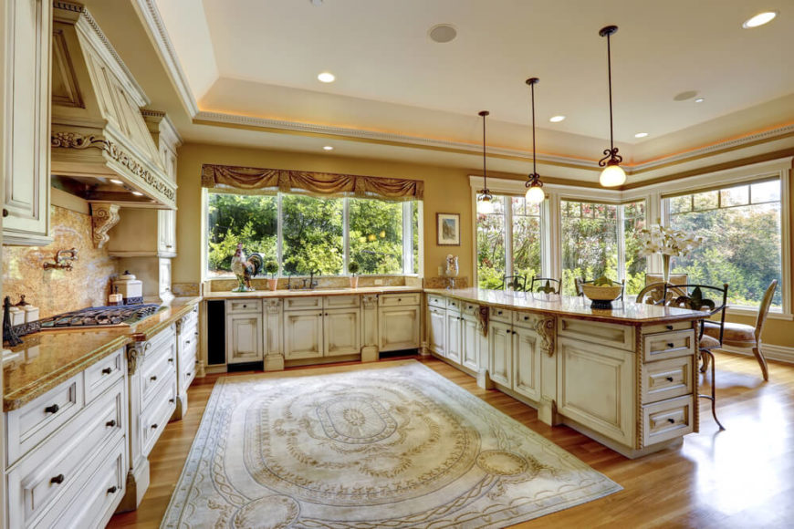 This country kitchen has a lavish atmosphere to it with it's rustic colored cabinets and a unique rug in the center of it. Large heritage picture windows filter in copious amounts of lighting and give the entire kitchen a terrific glow.
