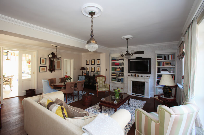 This more eclectic styled living room features dark wood floors with little variation in tone, which allows patterns in the furniture to be more varied and still not compete.