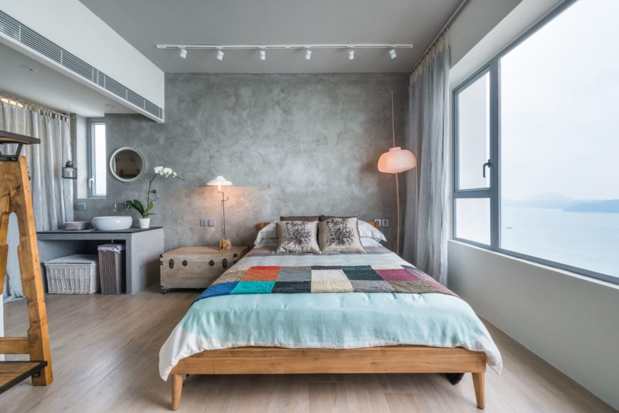 Not only is the bed frame of wood construction, but the wicker baskets in the corner and the chest, acting as a bed stand, are as well. The far wall is finished with cement to resemble a stucco-like quality.